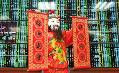 A performer dressed as the god of fortune holds prosperous signs in front of an electronic board displaying stock information at a brokerage house in Taipei February 5, 2014.