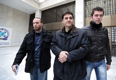 The former chief executive of the Hellenic Postbank, Angelos Filippidis (C) is escorted by plain cloth policemen outside the Athens police headquarters on February 5, 2014.