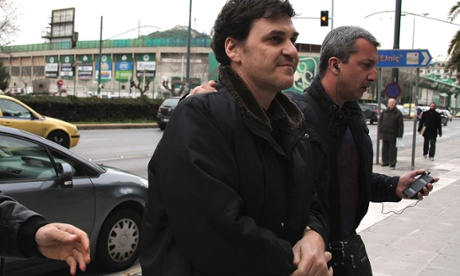 The former head of Greece s Hellenic Postbank, Angelos Filippidis, left, is led to police headquarters in Athens after his arrest on charges of providing unsecured loans to businessmen during his tenure, on Wednesday, Feb. 5, 2014.