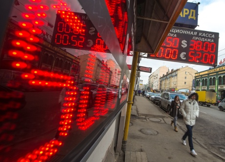 People walk under under a board listing foreign currency rates against the Russian ruble just outside an exchange office in central Moscow on March 3, 2014