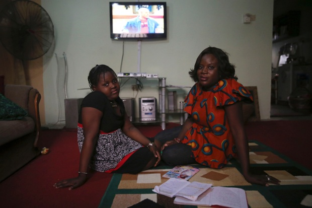 Adetola Ibitoye, 39, sits with her daughter Iteoluwa Ibitoye, 9, in their home in Omole district, Lagos. When Adetola was growing up, she wanted to run a fashion business. Now she is a clothes designer. Adetola says she wants her daughter to be the best at whatever she sets her mind to be. Iteoluwa says she wants to grow up to be a university teacher.