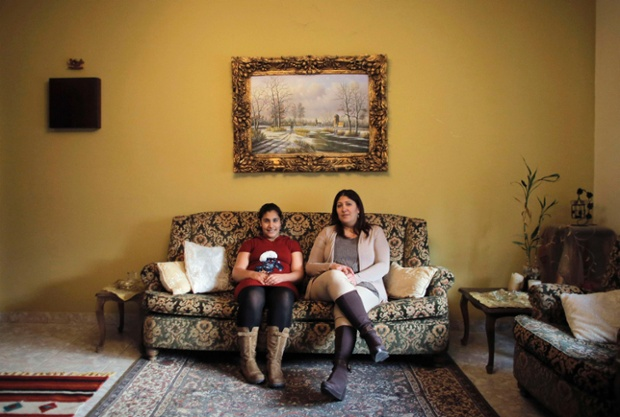 Hala Tanmus, 40, and her daughter Maya, 10, pose in the living room of their home in the West Bank city of Ramallah. Hala is a secretary who finished her education at age 20. When she was younger she wanted to become a lawyer. She hopes that her daughter Maya will become an interior designer. Maya, who says she will finish education age 20, would also like to become an interior designer.