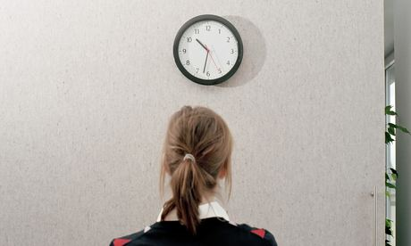 Woman in an office looking at a wall clock