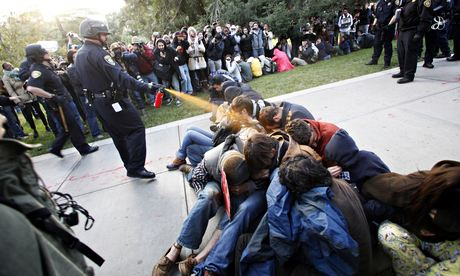A police officer uses pepper spray on protestors at the University of California