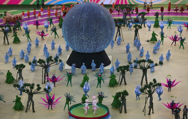 Dancers dressed as Amazon vegetation around something that might be a snow-dome paperweight.