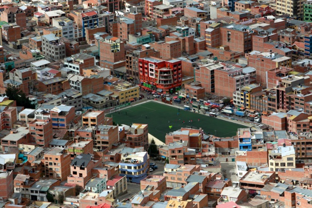 A football pitch surrounded by buildings in the middle of La Paz, Bolivia