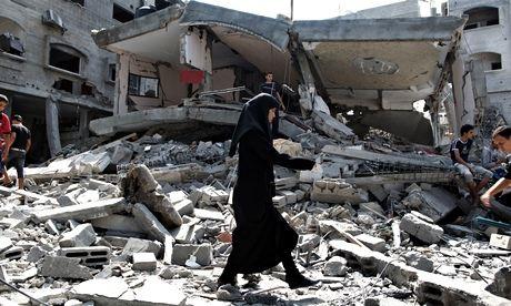 A woman walks on debris in Gaza