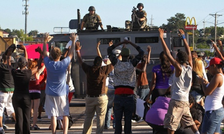 Protesters raise their hands in front of armed police in Ferguson.