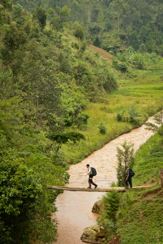 Lev Wood crossing a makeshift bridge over the river Mbriumbe River in Rwanda.