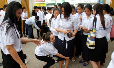 Proctors frisk students during the annual national high school graduation exam in Phnom Penh, Cambodia, Aug. 5, 2014. Cambodia has for the first time cleaned up the cheat- and bribery-ridden grade 12 national exams, a reform toward strengthening education quality.