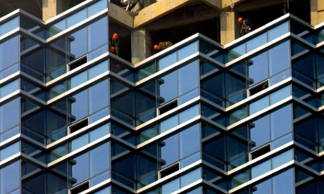 Workers install glass windows for a new building.