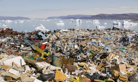 Rubbish dumped on the tundra outside llulissat in Greenland with icebergs behind from the Sermeq Kujullaq or llulissat Ice fjord. The Ilulissat ice fjord is a Unesco world heritage site