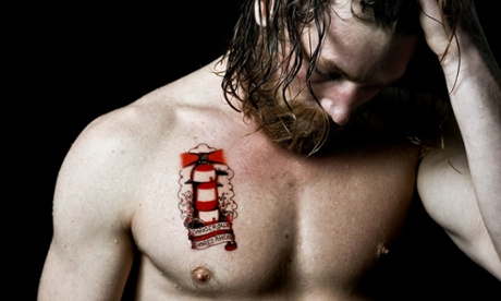 Surfer Ben Skinner with a tattoo highlighting the problem of marine pollution.