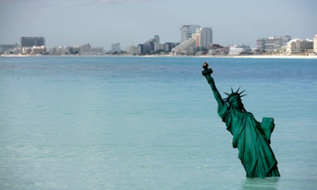 A cardboard version of the Statue of Liberty stands in the ocean at the Gaviota Azul beach in Cancun December 8, 2010. Greenpeace staged a performance sinking the world's best known landmarks in the ocean as climate talks take place in the beach resort.