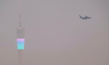 An airplane flies past the Canton Tower (L), or Guangzhou TV Tower, during a hazy day in Guangzhou, Guangdong province January 21, 2015.