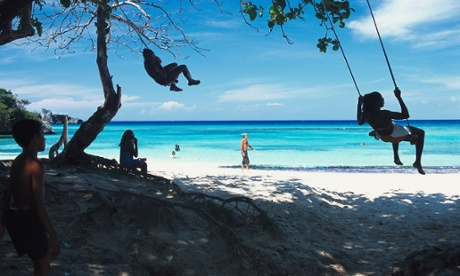 Children on swings at Winnifred Bay, Jamaica