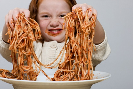 Girl holding up spaghetti covered, messily, in sauce, with her hands