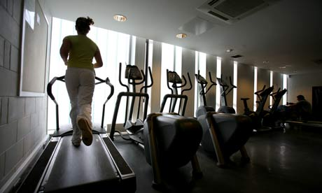 A woman exercises on a treadmill in a gym