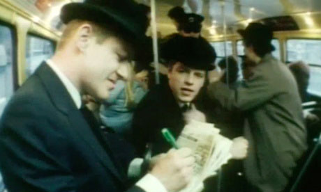 Suggs acts as a Greek chorus while an anonymous commuter struggles with a clue