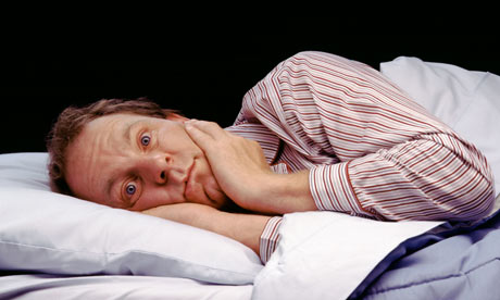 A man lying awake in bed looking anxious
