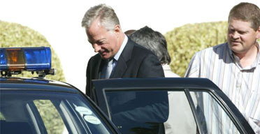 Mark Thatcher is escorted by police from his Cape Town home