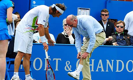 Andrew McDougall, a line judge at Queen's Club, shows David Nalbandian his gashed leg