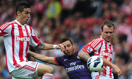 Geoff Cameron and Glen Whelan of Stoke City battles with Santi Cazorla of Arsenal.