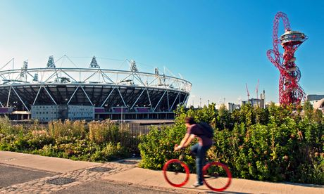 A Cyclist Rides Past The Olympic Stadium