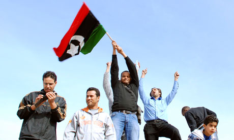 Protesters stand on a tank in Benghazi, Libya