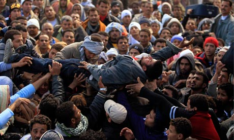 An Egyptian faints at the Tunisian border crossing of Ras Jdir