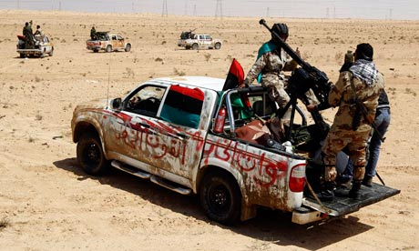 Rebel fighters ride in vehicles as they drive in the desert along the Benghazi-Ajdabiyah Road