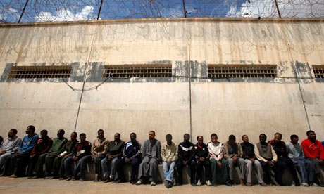 Mercenaries and forces loyal to Libyan leader Muammar Gaddafi sit inside a prison in Benghazi