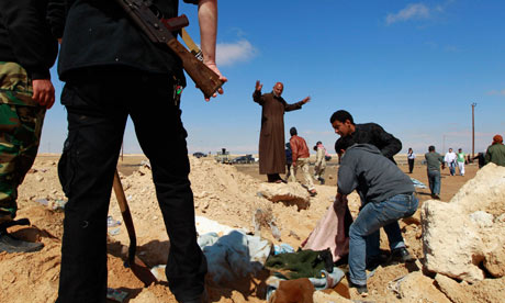 Rebels bury bodies following a Nato airstrike near Ajdabiya