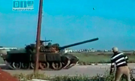 A man throws a rock at a tank in Deraa, Syria