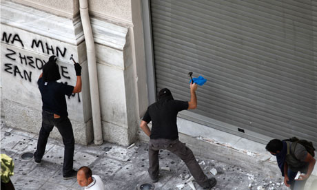 Demonstrators chip away at buildings to arm themselves with stones in Athens