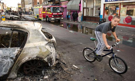 A boy cycles past a burnt-out police car after riots on Tottenham High Road