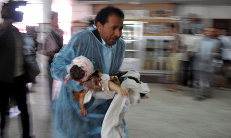 A doctor carries a wounded child in Sana'a, Yemen
